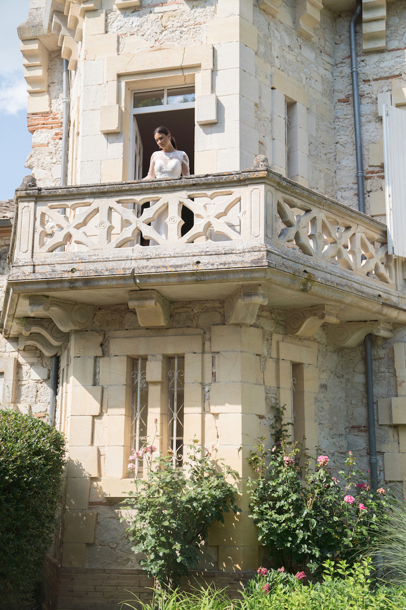 wedding venues in france - a bride on the balcony of chateau plombis