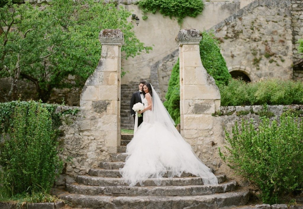 bride and groom on steps of french chateau featured