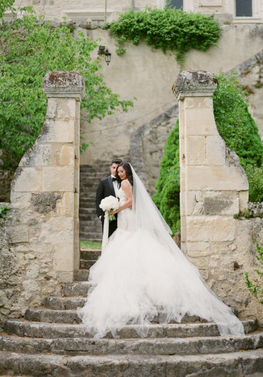 bride and groom on steps of french chateau